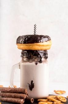 Вид спереди десерт в банке с пончиком и соломой