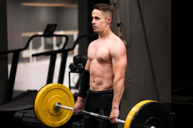 重量挙げのサイドビュー男性トレーニング