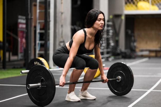 Тренировка женщины с тяжелой атлетикой