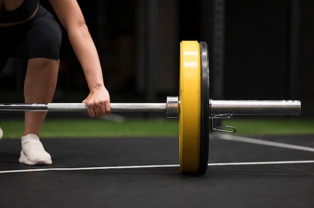 Тренировка молодой женщины конца-вверх с поднятием тяжестей