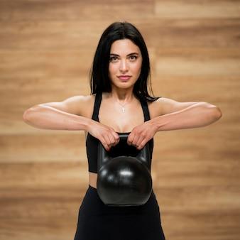 Вид спереди на тренировку женщины с тяжелой атлетикой