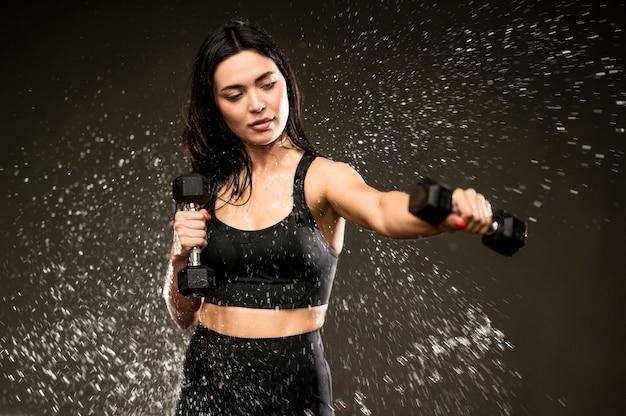 Тренировка женщины с ручными весами