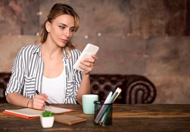 Внештатная женщина, проверяющая мобильный