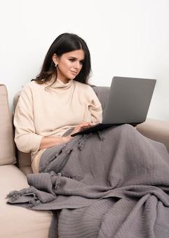 自宅で仕事のソファの上の女性