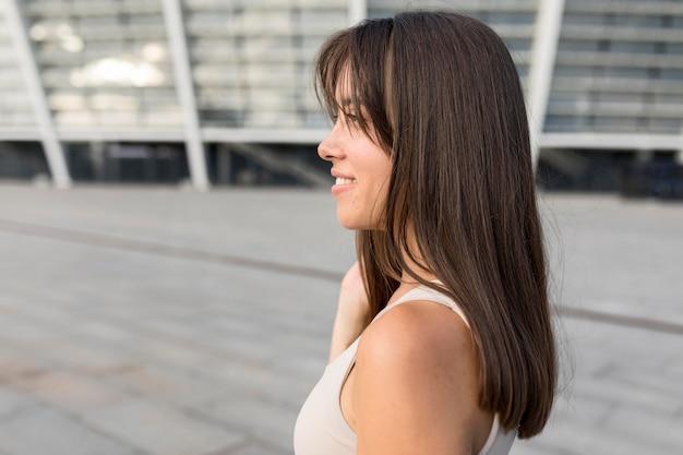 Боком красивая молодая женщина улыбается