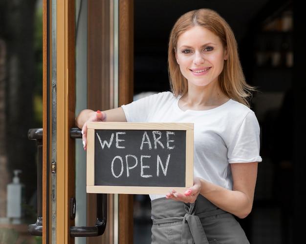 私たちはオープンサインを保持している女性