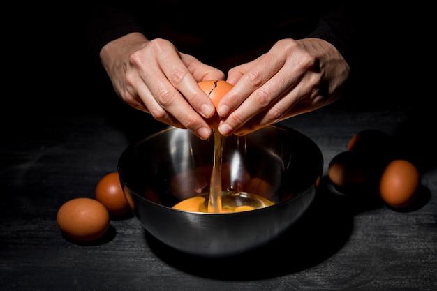 クローズアップの人が卵を割る