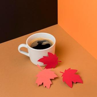 一杯のコーヒーの横にある紙の紅葉