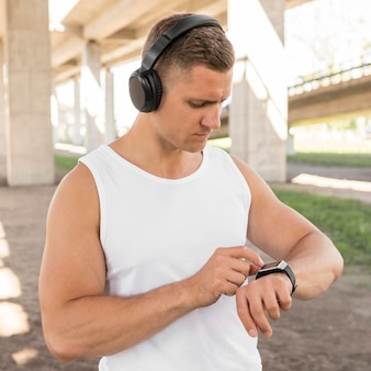 Человек использует свои умные часы перед тренировкой