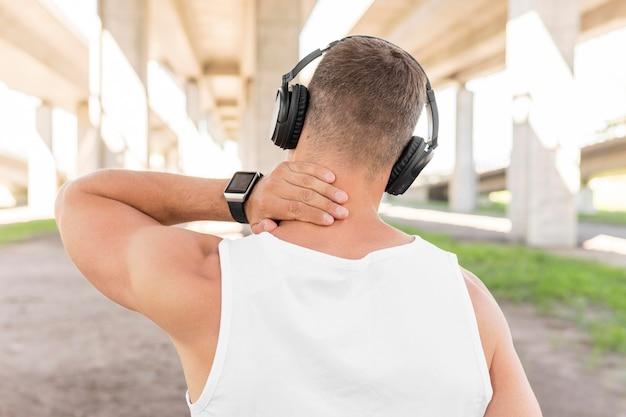 トレーニングの前にヘッドフォンで音楽を聴く背面図男