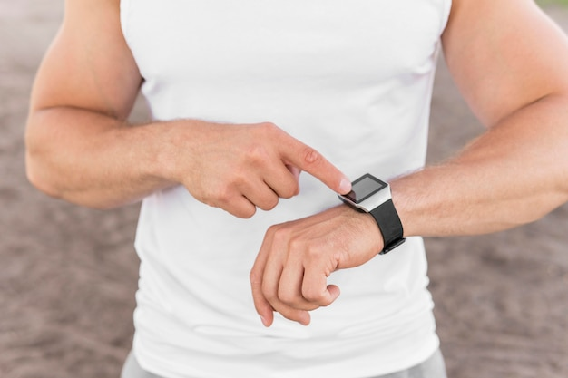 Спортивный человек, указывающий на его умные часы