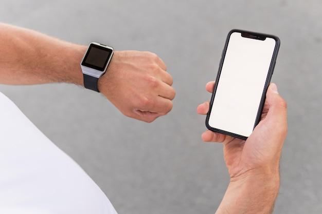 Высокий угол спортивная (ый) мужчина держит свой телефон с пустым экраном