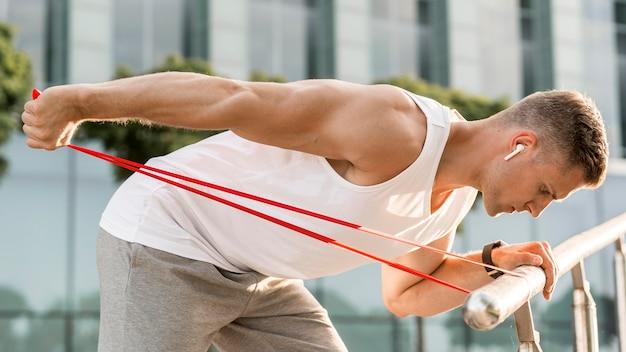 Боком спортивный человек тренируется на улице
