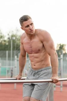 Атлетик тренирует человека без рубашки снаружи