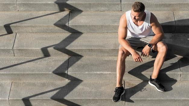 Человек вид спереди, сидя на лестнице с копией пространства