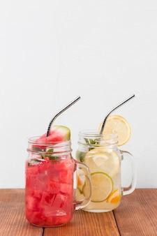 Баночки со свежими фруктовыми напитками на столе