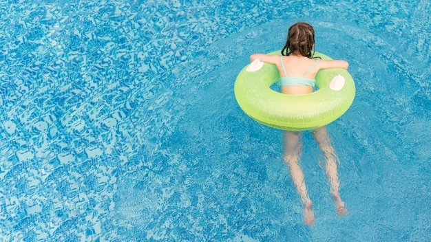 Высокий угол девушка в бассейне плавать
