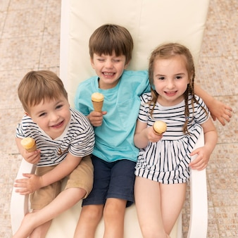 サンベッドに座ってアイスクリームを食べる子供たち