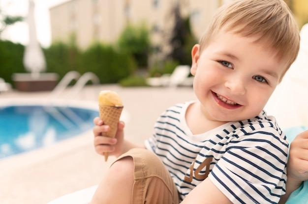 Улыбающийся мальчик ест мороженое