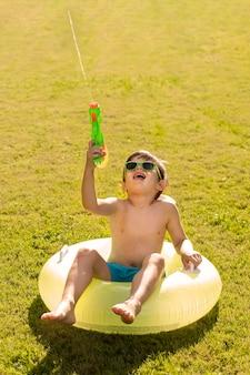 Мальчик в шляпе и очках играет с водяной пушкой