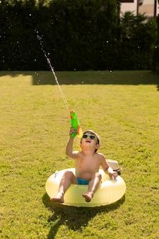 Мальчик в поплавок играет с водяной пушкой