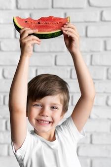 Маленький мальчик ест арбуз
