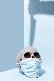 医療マスクと不気味なハロウィーンの頭蓋骨のクローズアップ