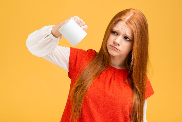 マグカップを保持しているミディアムショットの動揺の女の子