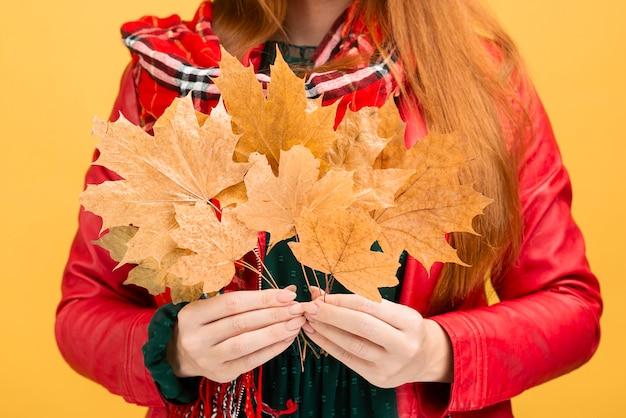 黄色の葉を保持しているクローズアップの女の子