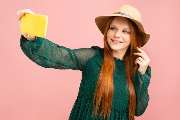 Средний снимок женщины, принимающей селфи