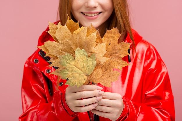 葉を保持しているジャケットのクローズアップの女性
