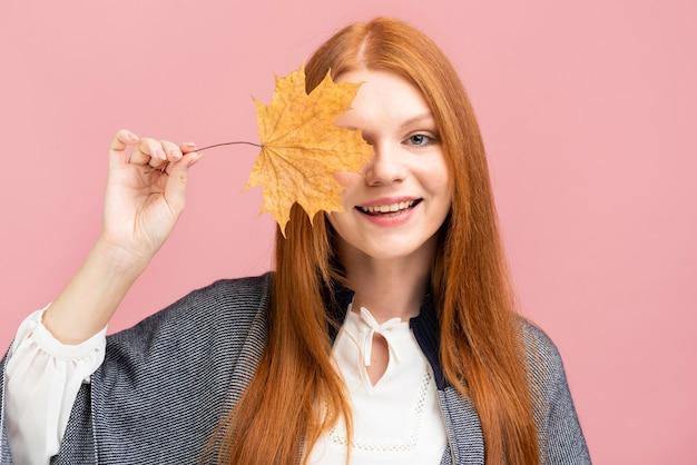 黄色の葉を保持している幸せな女