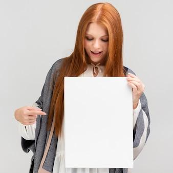 キャンバスを指すミディアムショットの女性