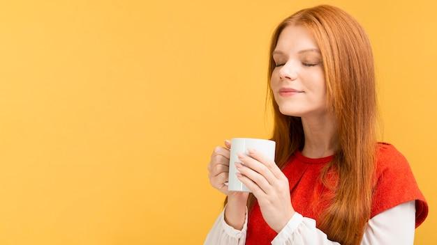 マグカップを保持しているミディアムショットの女性