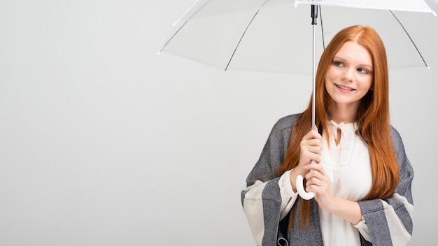 Улыбающаяся девушка держит прозрачный зонт