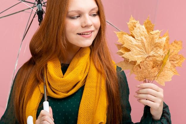 黄色の葉を保持しているクローズアップの女性