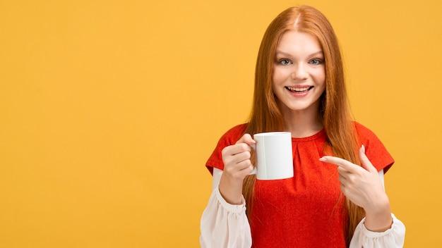 マグカップを保持しているミディアムショットのスマイリー女性