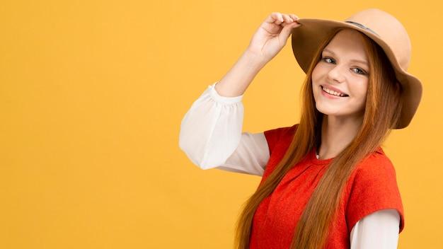ミディアムショットの笑顔の女性の帽子をかぶっています。