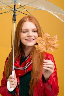 黄色の葉を見てスマイリー女性
