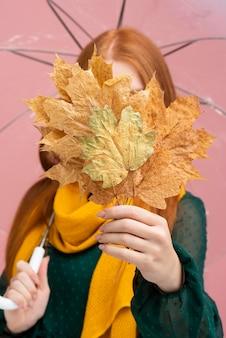 葉で顔を覆っている女性
