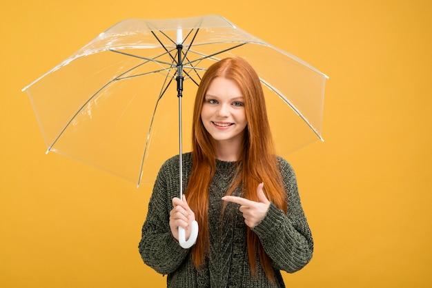 Женщина вид спереди, указывая на зонтик