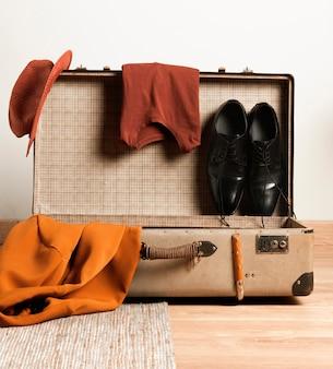 カジュアルな服でレトロなスーツケースをクローズアップ
