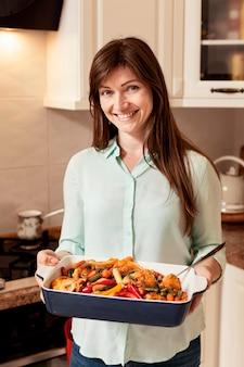 夕食のための食糧のトレイを保持している女性