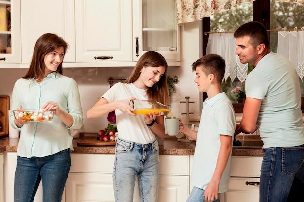 両親がキッチンで子供たちと食事を準備します。