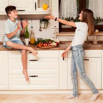 台所で野菜と遊んでいる子供たち