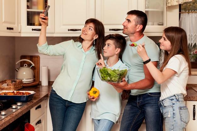 Мать, принимая селфи с семьей на кухне перед ужином