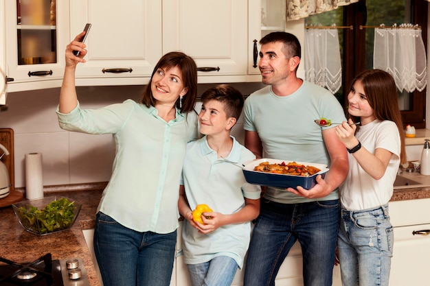 Семья, делающая селфи вместе перед обедом