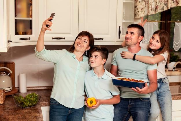 Семья берет селфи на кухне перед ужином