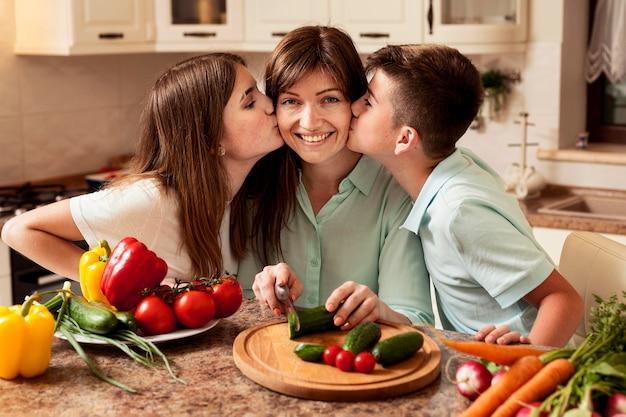 Дети целуют маму на кухне во время приготовления пищи