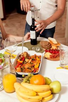 夕食の席でワインのボトルを開く男